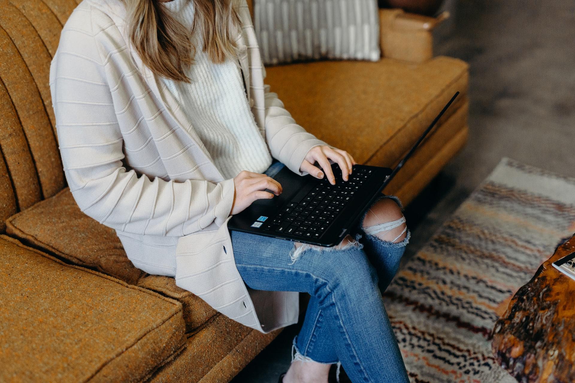 Frau mit Laptop auf Sofa. Symbolbild für die Teilnahme an einem Giving Circle. Foto: Brooke Cagle auf unsplash.com