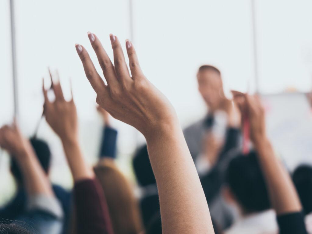 Menschen heben die Hände. Symbolfoto für Abstimmung bei Giving Circles. Foto: Momentum Fotograh/shutterstock.com